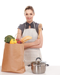 Woman in apron standing near table with grocery bag , isolated
