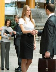 Businesspeople, or businesswoman and client handshaking