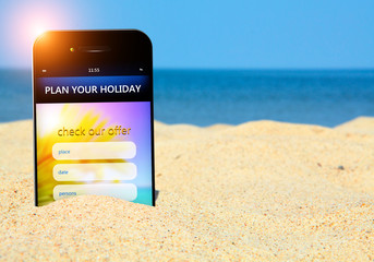mobile phone with holiday planner on the beach