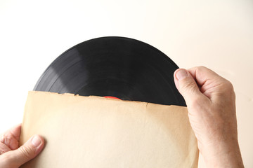 Man holds vinyl record in sleeve