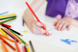 Fototapety Cute girl drawing a picture with colorful pencils