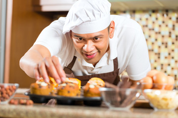 Asian man baking muffins in home kitchen