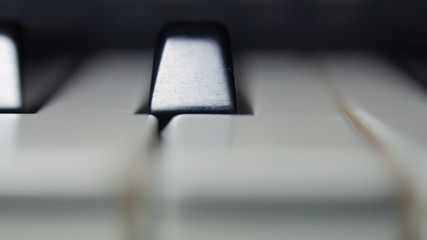 The camera shoots a close-up piano keys