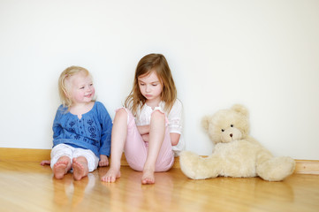 Two cute little sisters sitting on a floor