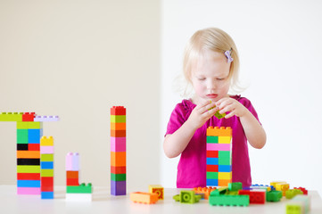 Cute toddler girl playing with colorful blocks