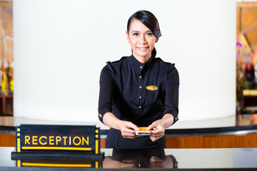 Asian woman in uniform at hotel reception desk