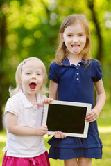 Two little girls holding tablet PC outdoors