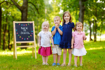 Four excited little kids by a chalkboard
