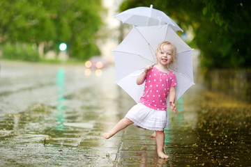 Cute little toddler girl having fun under a rain