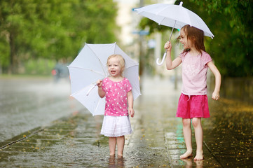 Two cute little sisters having fun under a rain