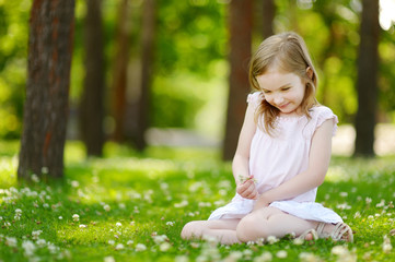 Cute little girl sitting on a clover field