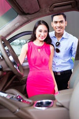 Asian couple choosing luxury car in dealership