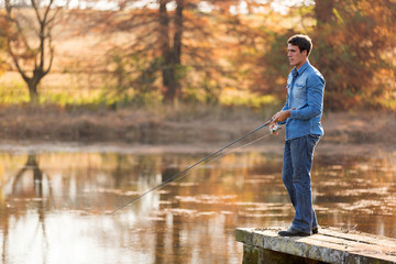 young man fishing by lake