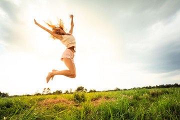 Jumping girl at field in summer