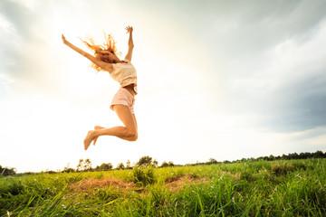 Jumping girl at field in summer