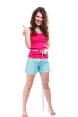 sporty fit woman with measure tape thumbs up