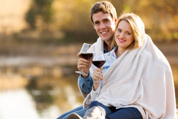 young couple snuggle outdoors with glass of wine