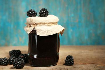 Tasty blackberry jam and fresh berries, on wooden background