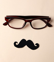 Glasses and mustache forming man face on beige background