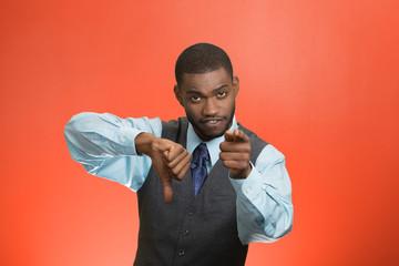 Upset company man giving thumbs down poiting at you