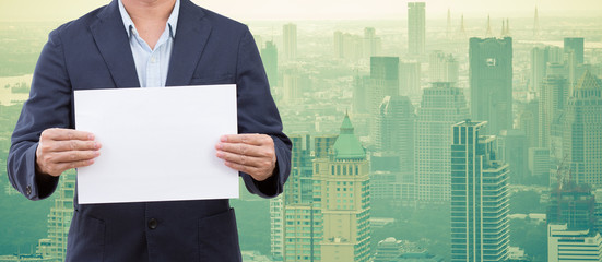 Business man hands holding blank paper with cityscape background