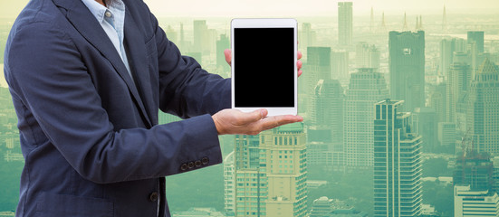 Business man hands holding tablet computer with cityscape backgr