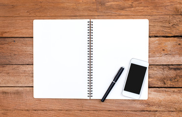 Notebook and smartphone with old wooden background