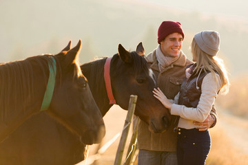 young couple petting a horse in a paddock
