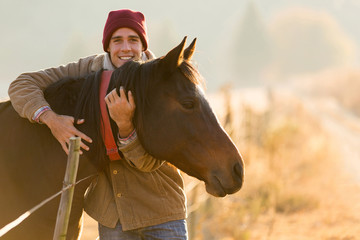 man hugging his horse