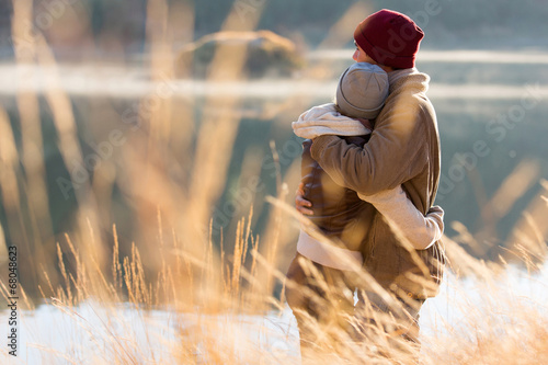 back view of young couple hugging in winter - 68048623