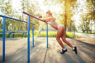 fitness woman relax after workout exercises on bars outdoor