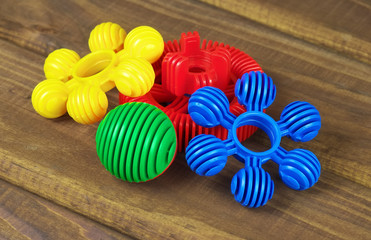 Multicolored toy parts of constructor on wooden background
