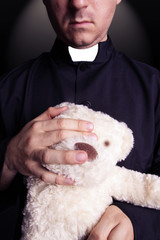 The priest holding a teddy bear