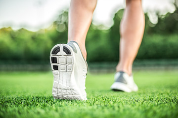 Runner feet running on green grass. closeup on shoe.