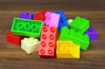 Toy colorful plastic blocks on wooden background