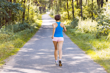 Sporty young woman runner running on the road in forest