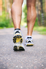 Jogging man. Running shoes and legs of male runner outside on ro