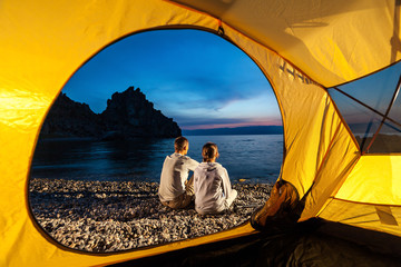 Couple sits near tent