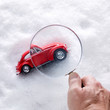 Checking a red car in snow with magnifier