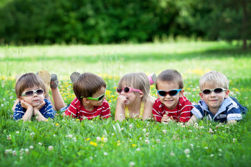 Five adorable kids, lying on the grass, smiling, having fun