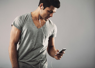 Young guy enjoying listening music on smartphone