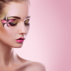 Young adult woman with closed eyes and creative makeup on pink b