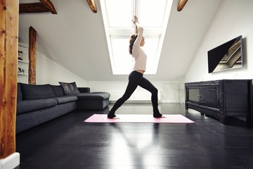 Fit young woman doing yoga at home
