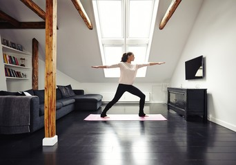 Healthy woman exercising in living room