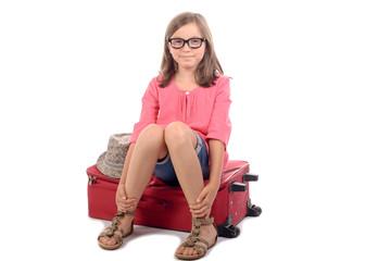 jeune fille assise sur une valise rouge