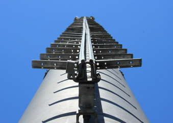 Metal ladder on chimney against blue sky
