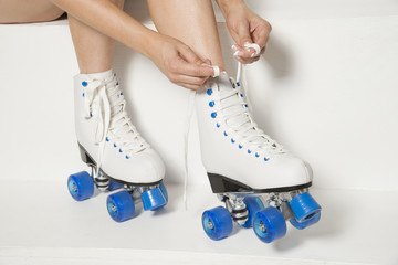 Roller skater tying laces on her quad wheel boots