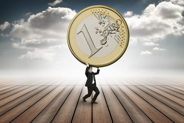 businessman is lifting up a huge euro coin