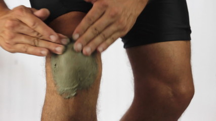 Male runner using therapeutic clay on his knee