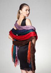 woman wearing a collection of scarves on grey background
